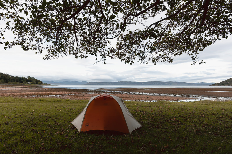 A tent is pitched on the grass behind the beach at Applecross Bay on the North Coast 500 Route.