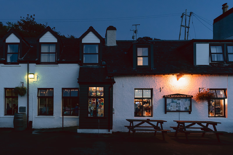 Applecross Inn with lights on both in and out as night approaches.