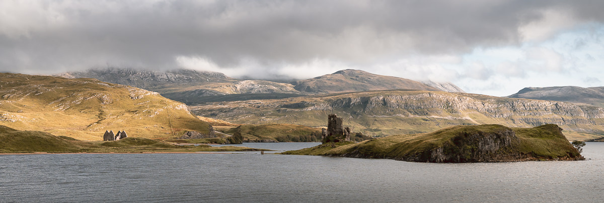 The ruins of Ardvreck Castle in the late afternoon light on Scotland's North Coast 500 route.