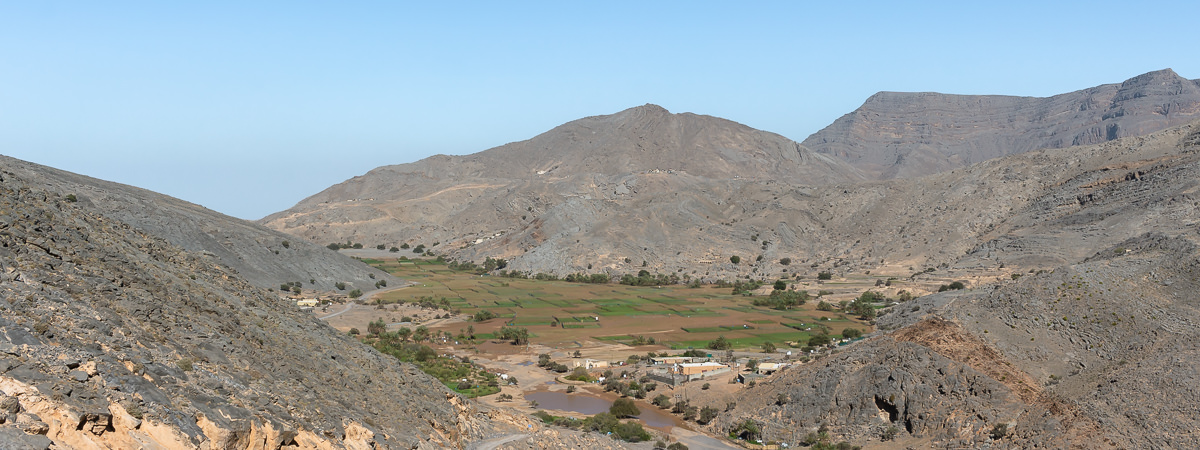 Looking back down on the green fields of the As Sayh Plateau from the mountain road, dusty brown mountains rising around it