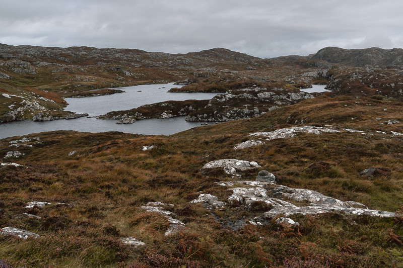 The unique landscape of small lochs and rocky hillocks in Assynt, seen on the Assynt coastal loop road section of Scotland's North Coast 500.