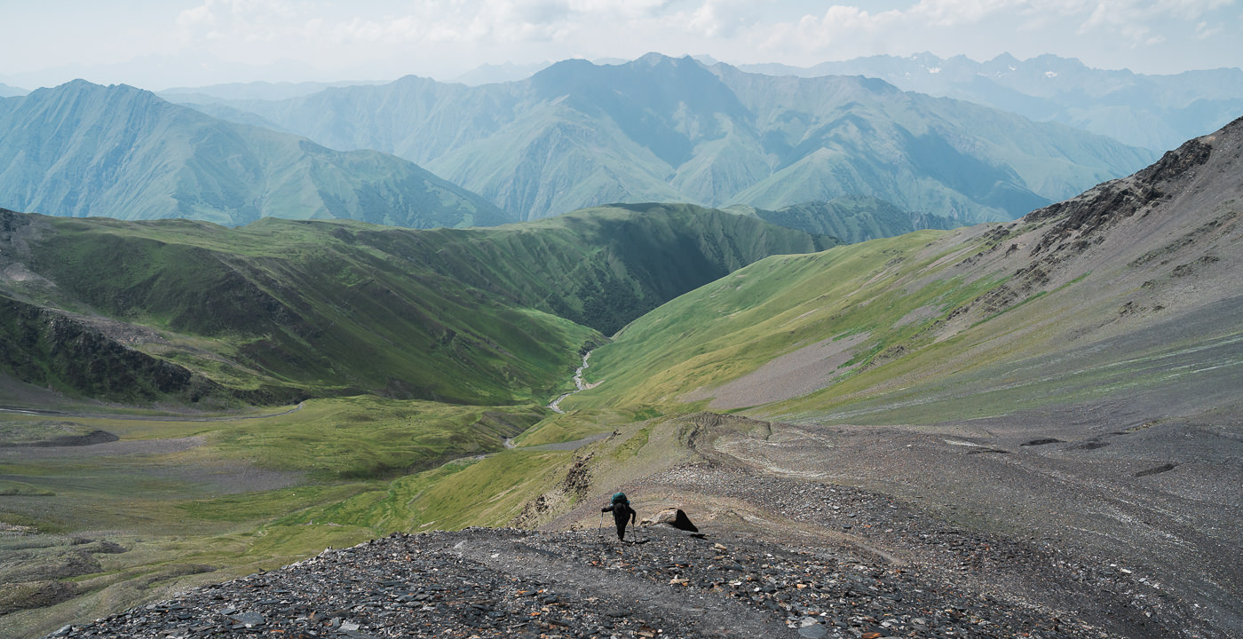 A hiker climbs the shale switchback trail to Atsunta Pass on the Shatili Omalo trek, with the layered mountains of Khevsureti behind