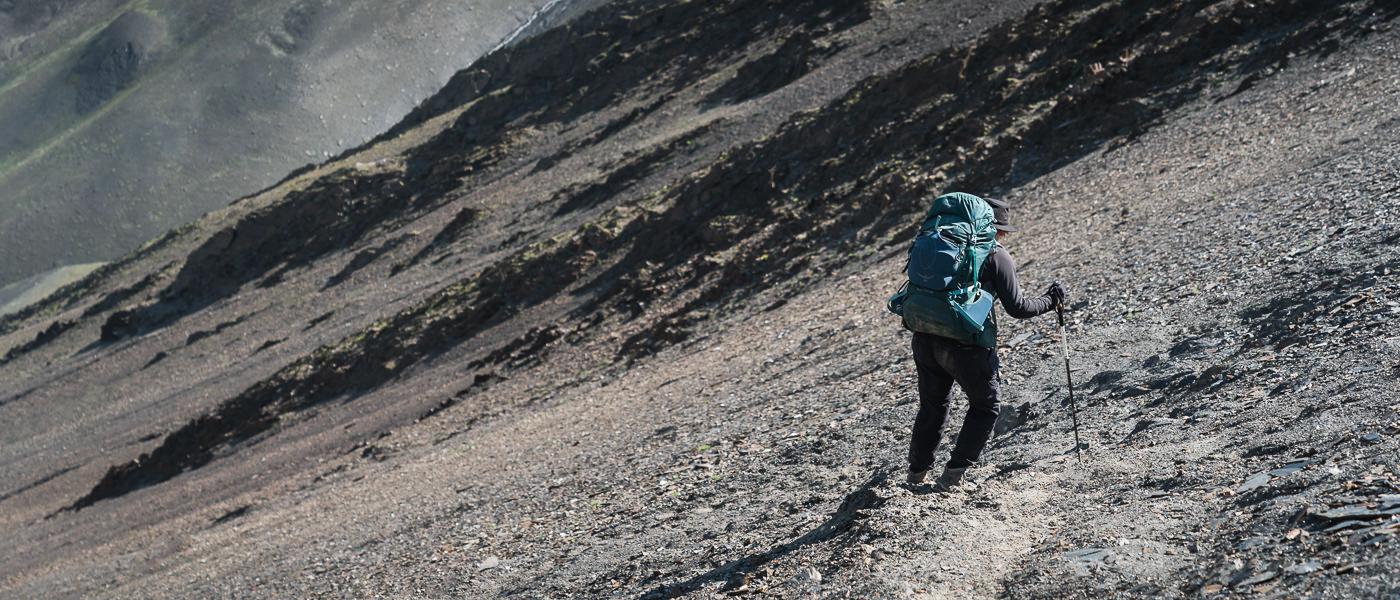 Descending into Tusheti from Atsunta Pass on the Shatili to Omalo trek, a hiker carefully negotiates the sandy shale covered slope