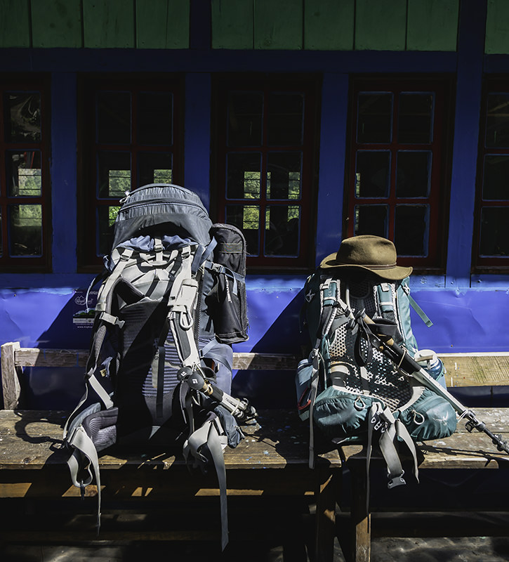 Two backpacks sit on a bench outside a lodge at lunchtime