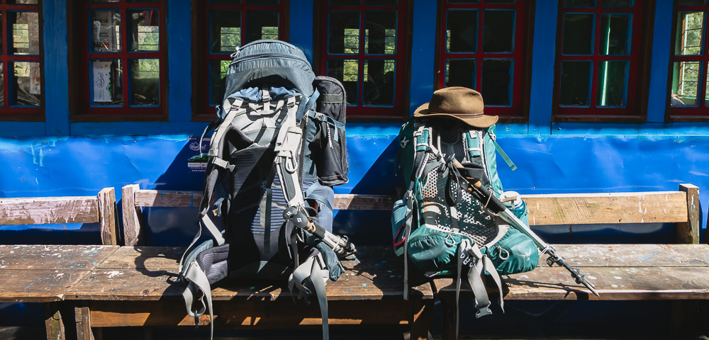 Two backpacks sit on a bench outside a lodge in Nyak Phedi on the Manaslu Circuit Trek in Nepal