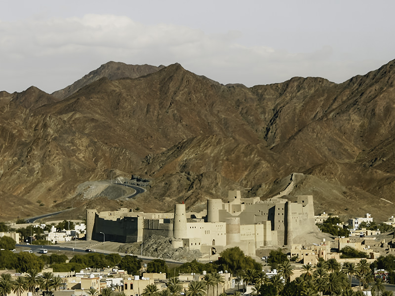 The large sandy coloured Bahla Fort dominates the landscape in Bahla, Oman. The fort is surrounded by low houses and date palms, and the mountains rise behind