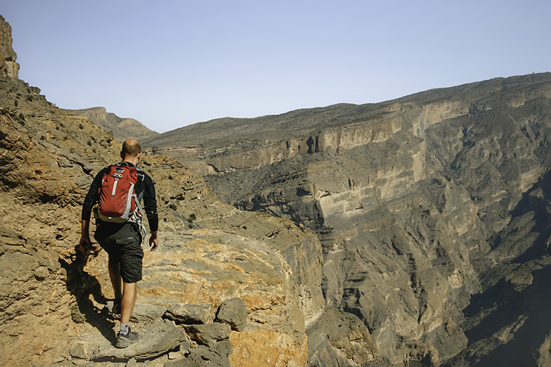 A person with a small red backpack sets out on the balcony walk at Oman's Grand Canyon, below Jebel Shams, Oman's highest mountain. The narrow rocky path falls off to the right in a sheer drop. This is one of the best places to visit in Oman.
