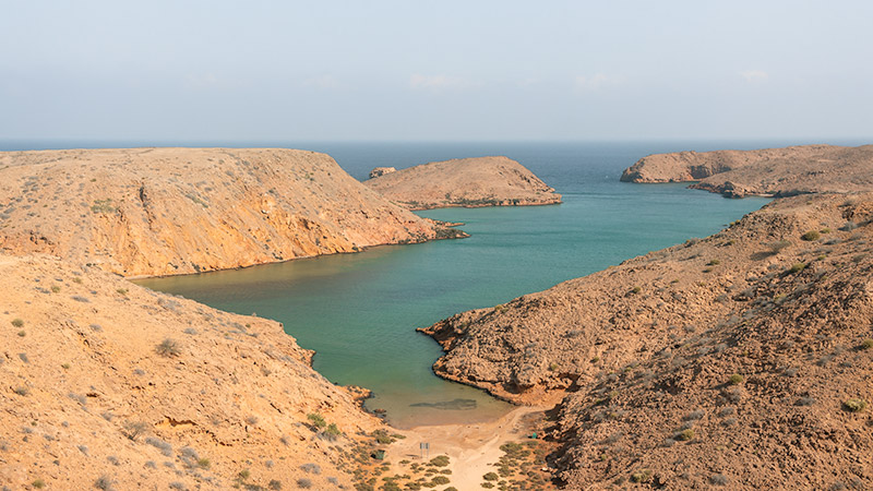 Sandy rocky coastline forming an inlet full of sparkling aquamarine water at Bandar Al Khiran in Oman
