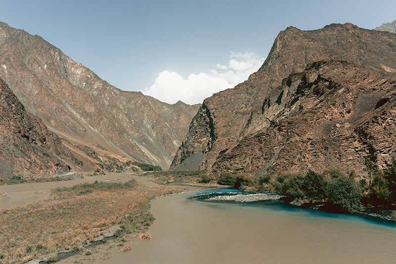The bold blue water from the Jizeu valley meets the muddy brown of the Bartang River. Bare and dry brown mountains rise skyward.