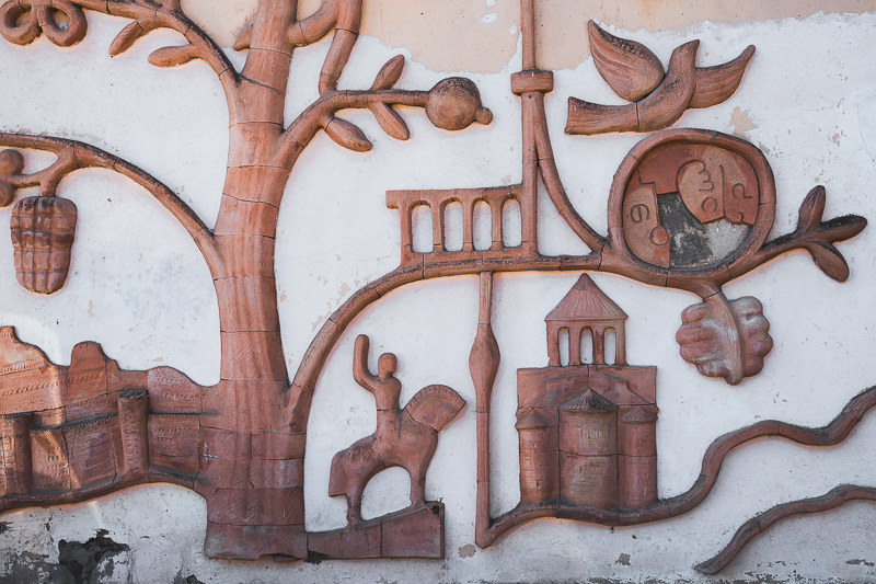 The base of a huge bas relief of a tree with Georgian symbols, on a building wall in Kojori Town Centre, Georgia
