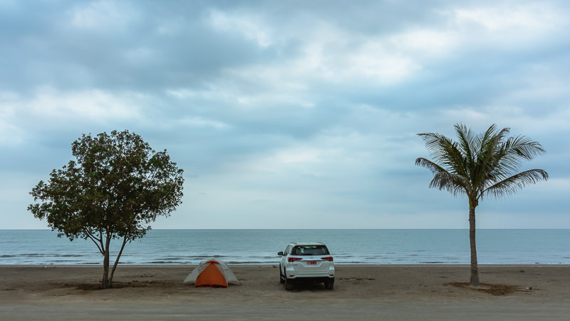 A 4WD and a tent between two trees at dusk on a beach in northeastern Oman