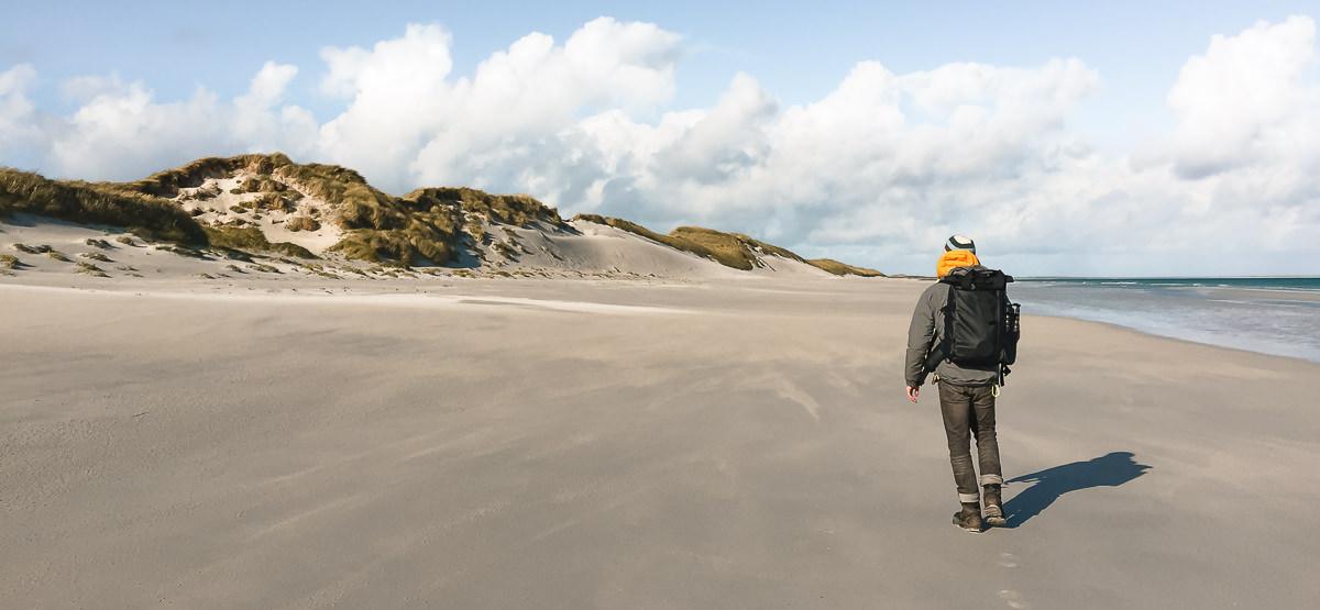 A person wearing a Wandrd Prvke camera bag walks along an empty beach on Sanday in the Orkney Islands