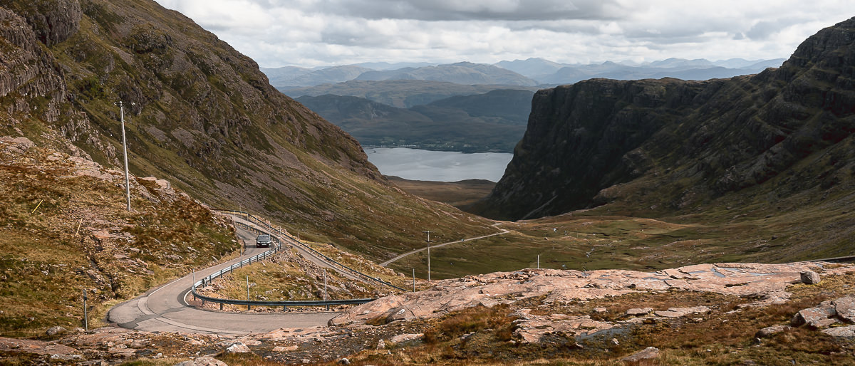 A car winds round one of the final bends on the climb towards the Bealach na Ba, one of Scotland's most scenic roads and a true highlight of the North Coast 500.