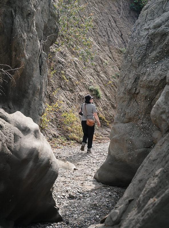 A hiker walking a narrow trail between high rock walls in Bear Canyon in Vashlovani National Park, Georgia