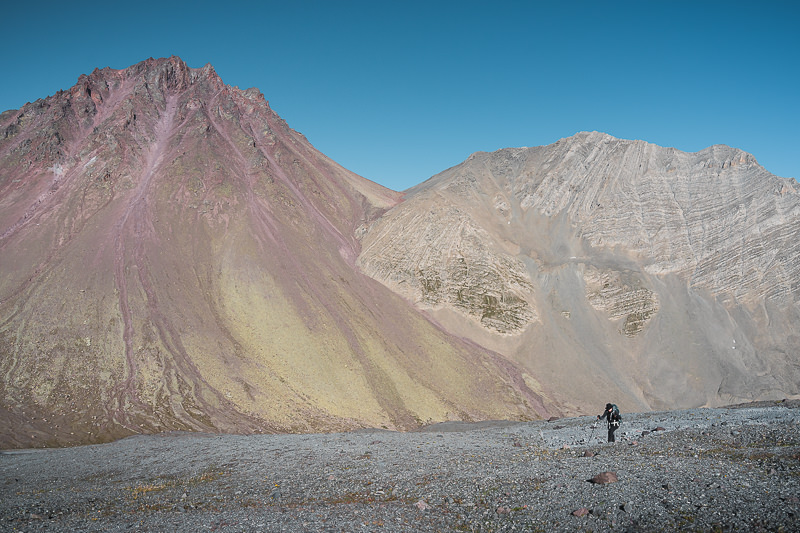 A hiker skirting the base of Sherkhota on the final climb to Kelitsadi Lake, after the steep descent from Khorisar Pass (seen behind)