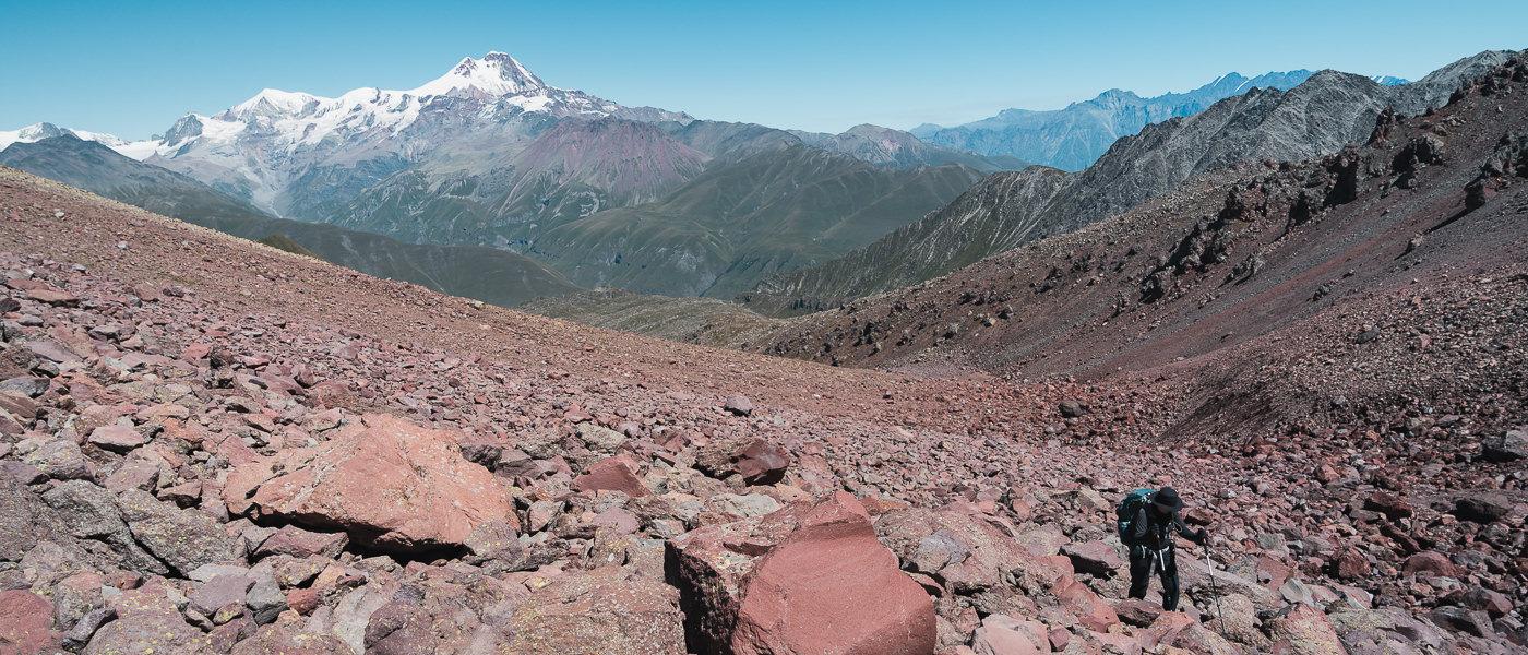 A hiker climbs over jumbled reddish rocks with mountains all around, on Day 2 of the Kelitsadi Lake Trek