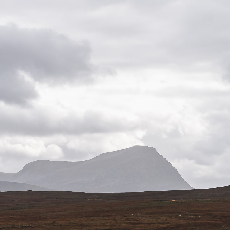 A hazy Ben Hope marks the skyline across the moors, seen from the North Coast 500 route in Scotland
