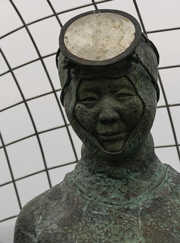 A close up head shot of a haenyeo statue at Beophwan Port on Jeju Island