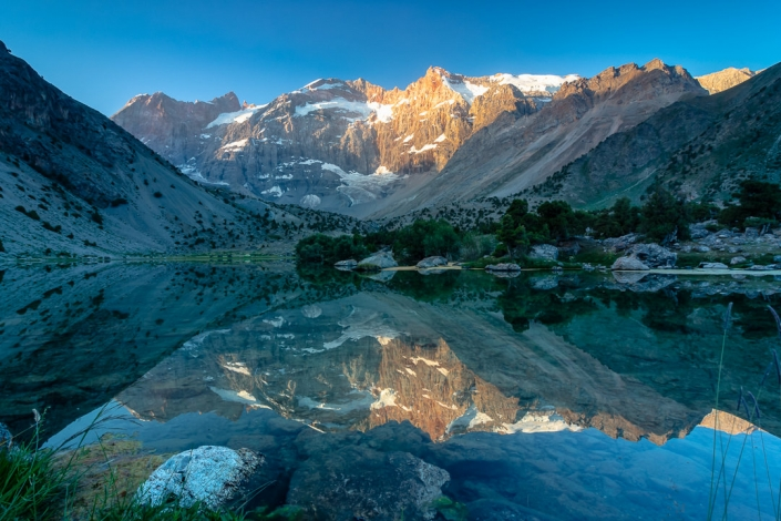 The rising sun lights up the mountain peaks as the landscape is reflected in the perfectly still surface of Bibidzhonat Lake in the Fann Mountains of Tajikistan
