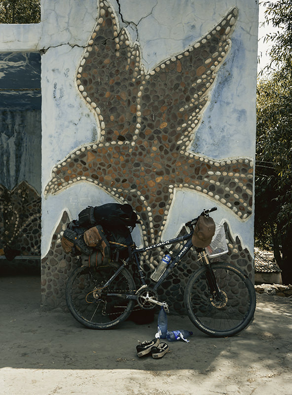 A touring bike laden with bags rests against a Soviet bus stop with an eagle mosaic on a Pamir Highway road trip