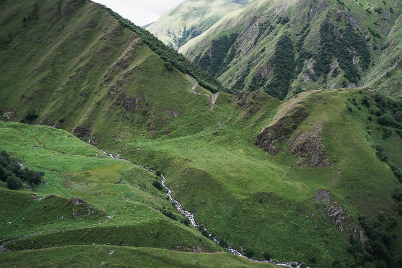 The trail crosses the 'big stream' and winds up the hillside into the forest beyond on Day 2 of the Tusheti to Pankisi Valley trek