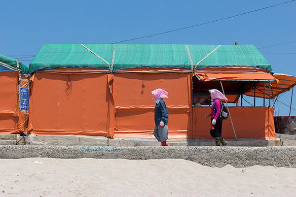 Bijindo: Two local women protected from the hot sun walk in front of a sashimi shack