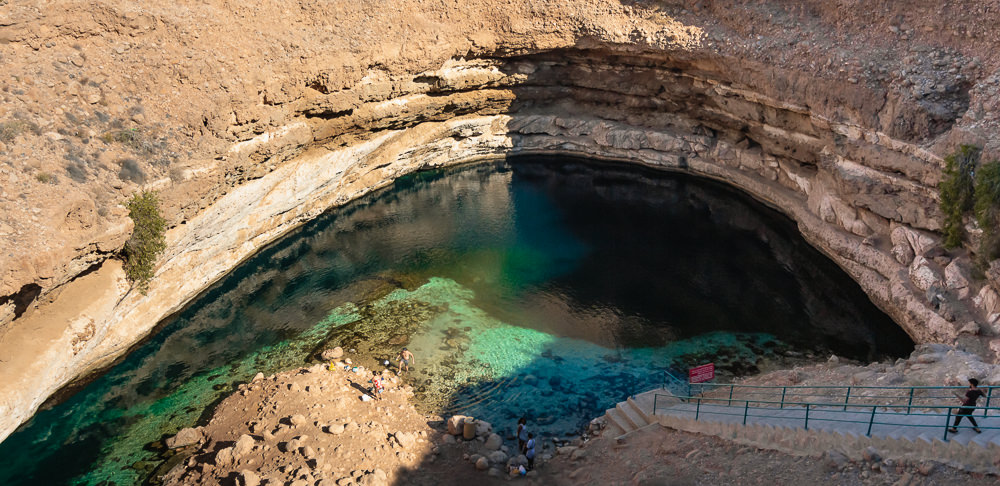 An early morning view down into the Bimmah sinkhole on day 3 of a 10 day Oman Itinerary. A few people are preparing to swim in the aqua water but it's quiet otherwise.