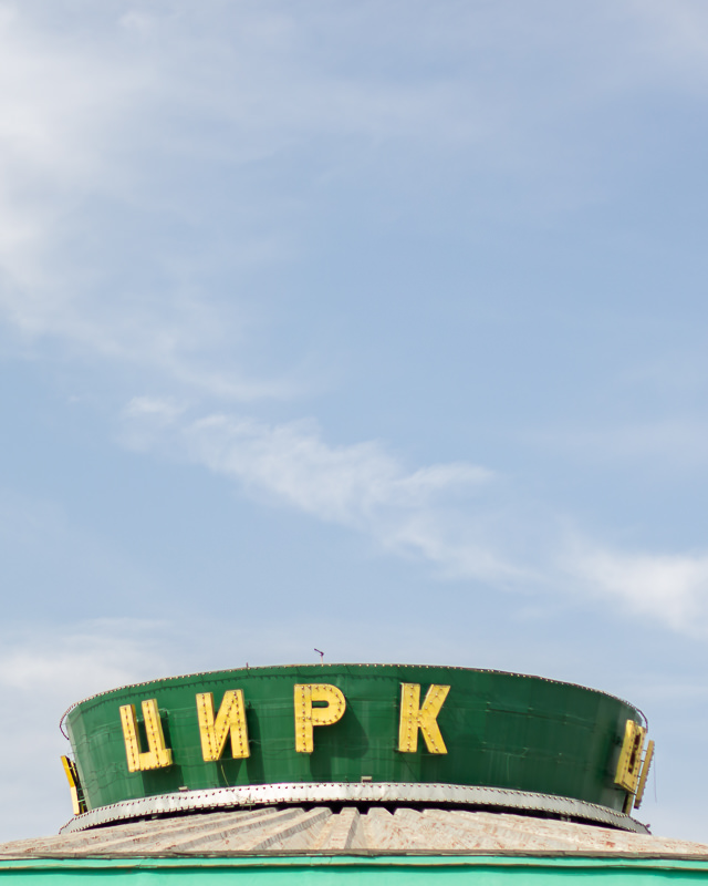 A minimal shot of the green top of the Soviet era State Circus in Bishkek, with Russian letters in yellow and a blue sky background