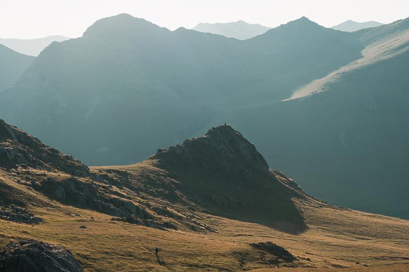 A hiker walks through golden brown grass at sunset with mountains rising behind, on the Black Rock Lake trek in Lagodekhi National Park