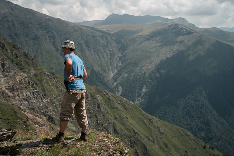 A local guide standing at a viewpoint where you can see mountains in neighbouring Dagestan and Azerbaijan, on Day 2 of the Black Rock Lake trek in Lagodekhi National Park