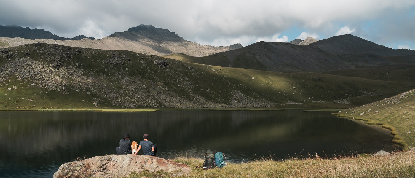 Two hikers and a dog rest on a rock in front of an unnamed lake on the Black Rock Lake trek