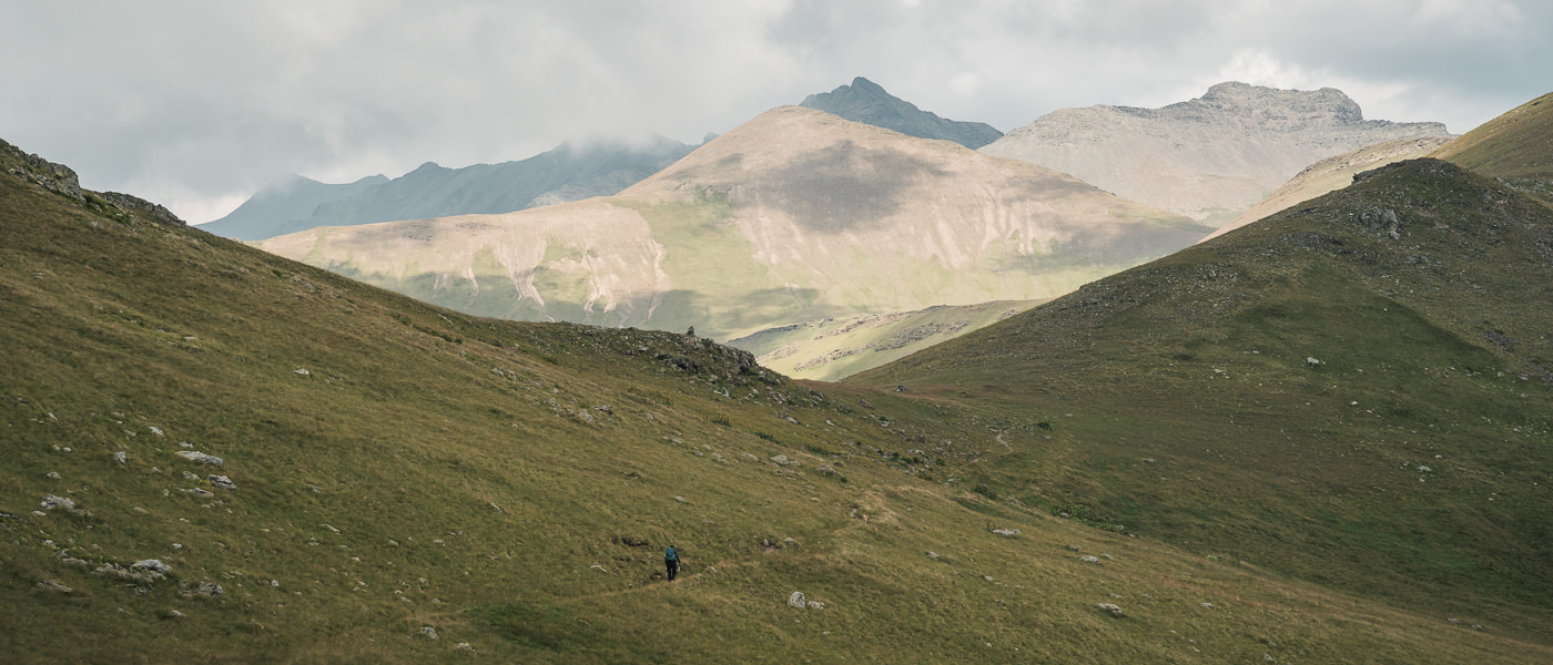 With the bulk of the climbing done, a hiker traverses the grassy high altitude hillsides on an easy trail towards Black Rock Lake