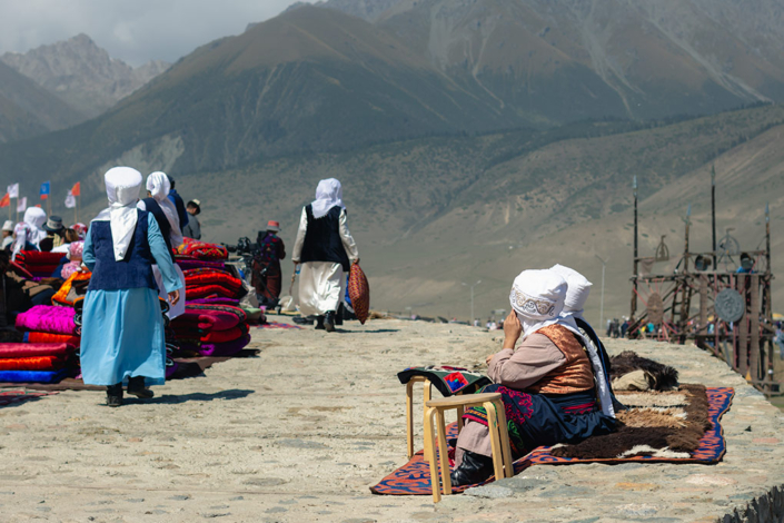Two women take a rest as others pass piles of folded blankets, heading towards the arts and crafts contests.