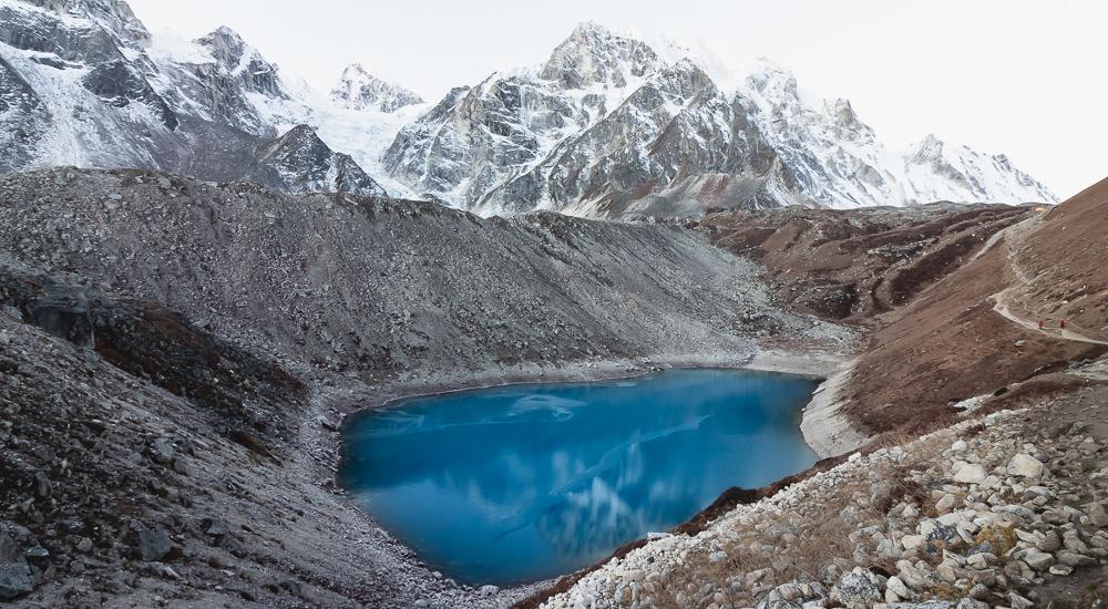 Bold blue lake beneath a snowy Larke Peak at daybreak on the Manaslu Circuit Trek