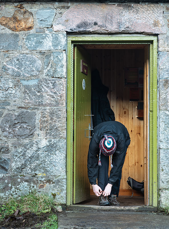 Taking muddy boots off at the distinctive green door of Gleann Dubh-Lighe Bothy