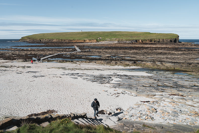 People make their way to and from the Brough of Birsay, a tidal island accessible at low tide via the man made causeway connecting it to Orkney Mainland