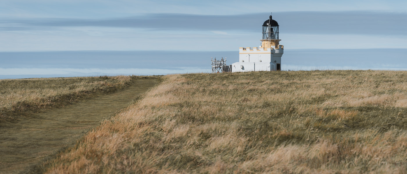 The white and yellow Stevenson lighthouse on top of the Brough of Birsay in the Orkney Islands