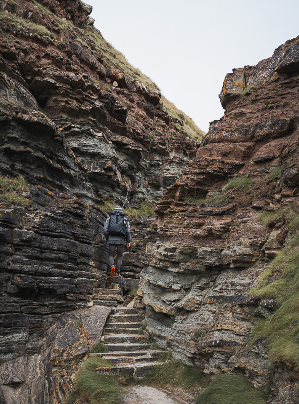 A person climbing stone steps through a narrow rocky gap to get onto the Brough of Deerness in the Orkney Islands