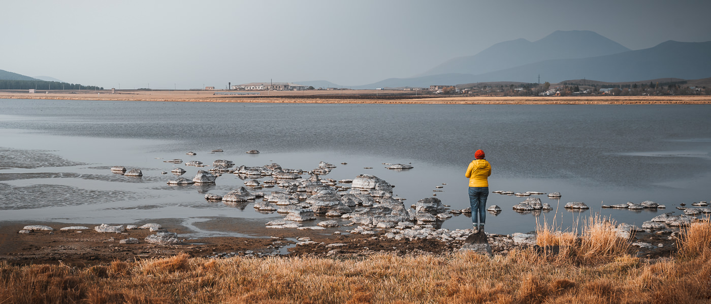 A person stands on a rock at the edge of Bughdasheni Lake in Javakheti