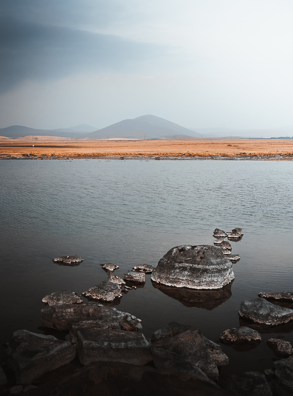 A string of rocks extends out into the water on Bughdasheni Lake in Javakheti