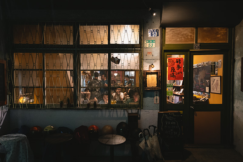 The outside of Cafe Flaneur in Tainan at night. A busy scene can be seen through the alley facing window, a warm light welcoming in the dark.