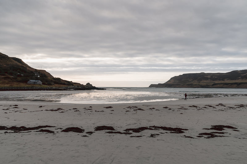 A person walks on the wide beach on an overcast afternoon at Calgary Bay on the Isle of Mull in Scotland.