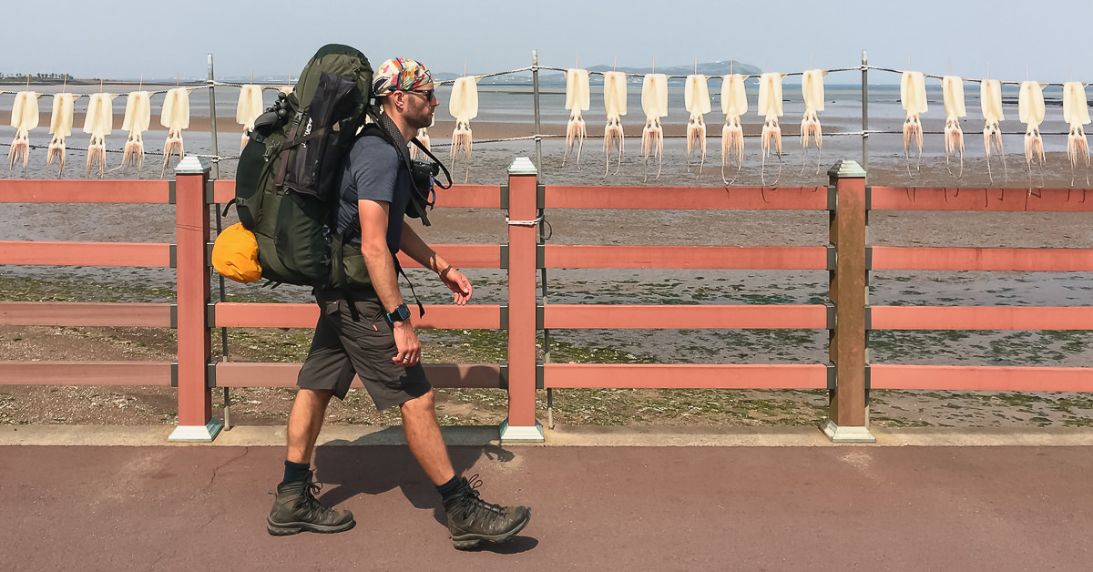 A hiker with a big backpack walks past drying squid on the coast of Jeju Island. A large camera is attached to one of the straps using a Peak Design Capture Clip, an essential item of travel photography gear