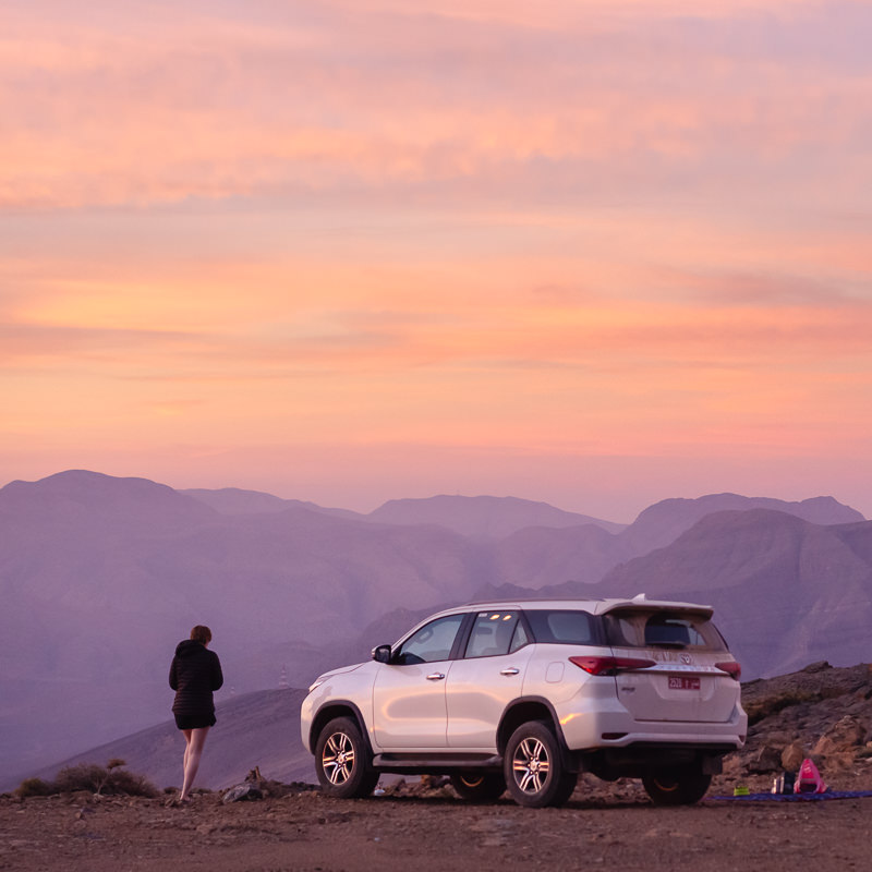 Pinks and yellows light the sky at sunrise in the mountains of Musandam. The flat area shows our campsite where our Toyota Fortuner gleam in the morning light.