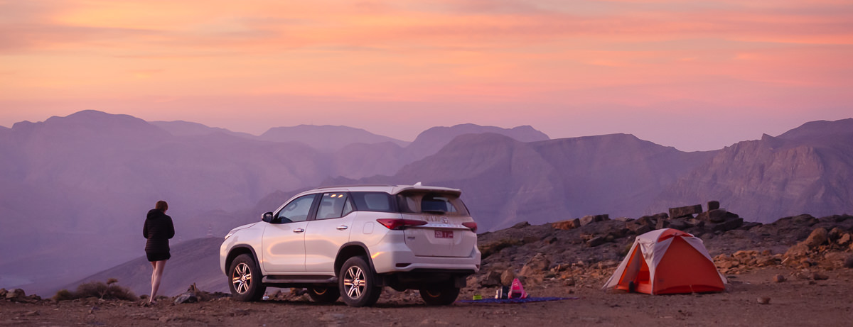 Pinks and yellows light the sky at sunrise in the mountains of Musandam. The flat area shows our campsite where the tent and our Toyota Fortuner gleam in the morning light.