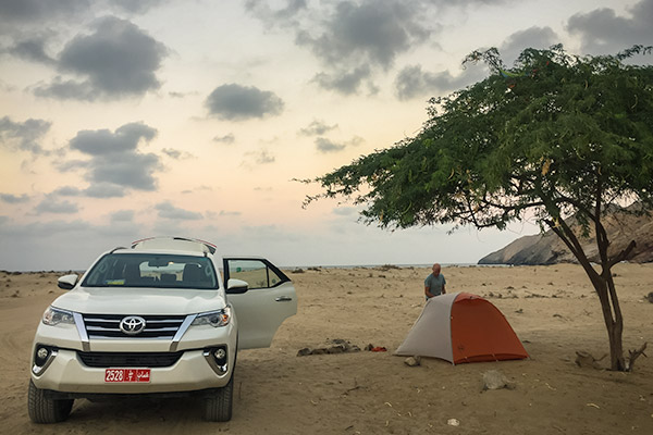 Our grey and orange Big Agness tent is set up under a tree on Yiti Beach in Oman, with our rental Toyota Fortuner parked alongside.