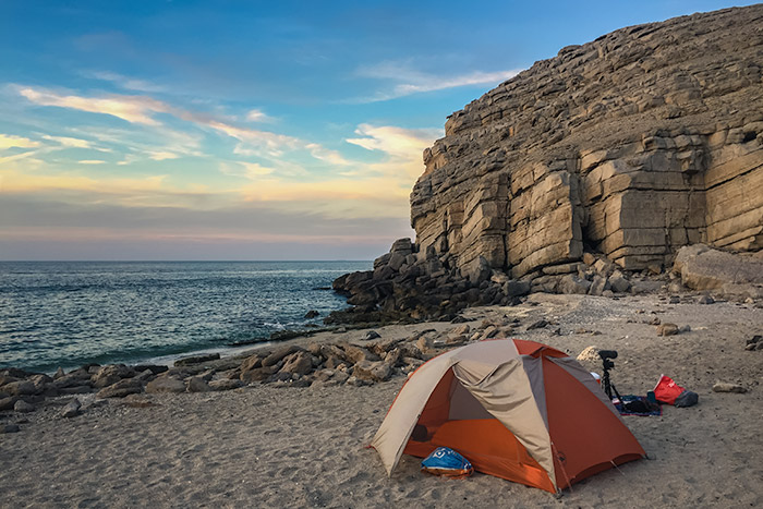 The Big Agnes Copper Spur tent pitched on the sand of Rocky Beach in Musandam, limestone cliffs rising behind.