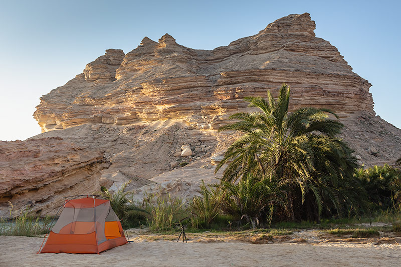 The tent sits on the sand next to palm trees, in front of an imposing rocky outcrop in Oman