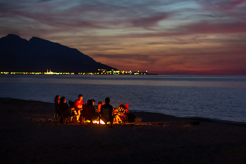 A family sit around a campfire on the beach with the lights of a distant town glimmering in the distance