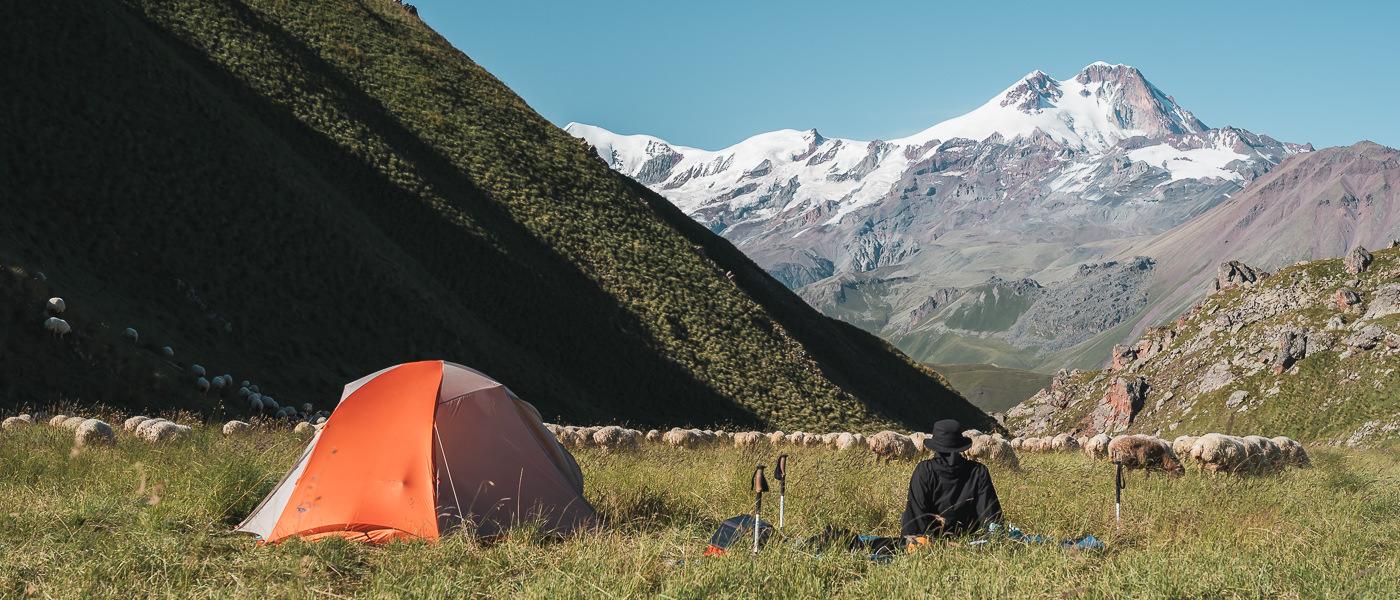 A hiker and her tent on the Keli plateau, camping on Day 1 of the Kelitsadi Lake trek